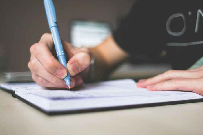 person writing editing or proofreading